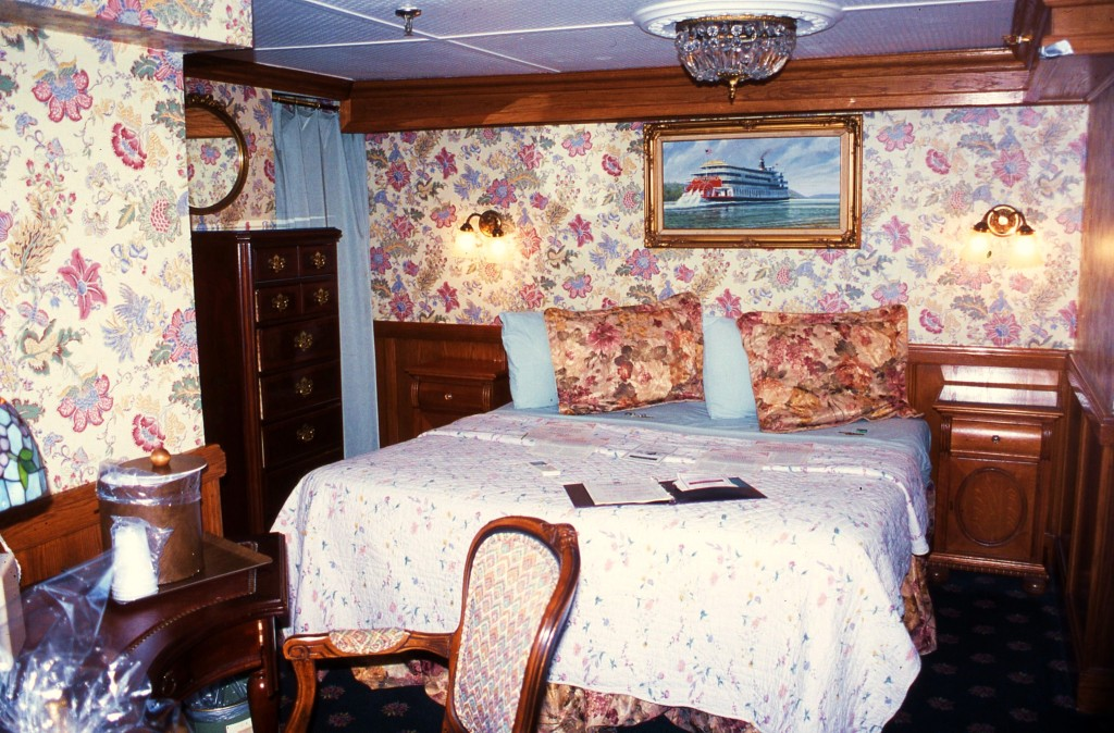 A stateroom aboard the AMERICAN QUEEN with a reminder of her predecessor DELTA QUEEN seen in the painting above the bed. * Photo: Ted Scull